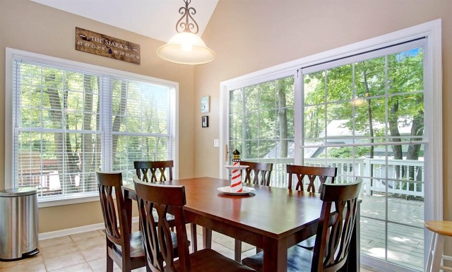 The dining area includes a table for six and barstools for four