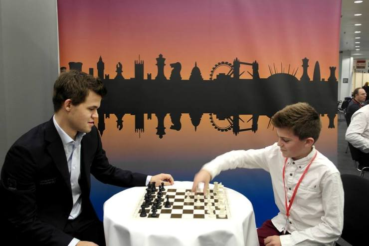 Magnus Carlsen plays with a young chess player, prior to one of his matches at the Chess Classic picture: Fiona Steil-Antoni