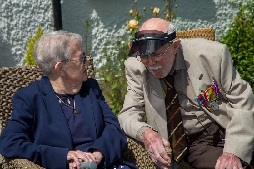 """Kitty Francis and Dennis Tidswell, sit talking at """"Our Greatest Generation,"""" an Age Cymru Dyfed event commemorating the 77th anniversary of D-Day. June 6th, 2021."""