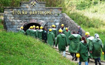 people in green coats entering a mine