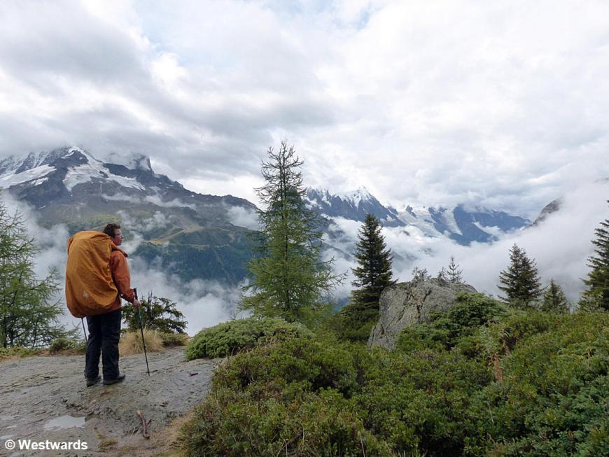 Hiker looking over clouds and mountains