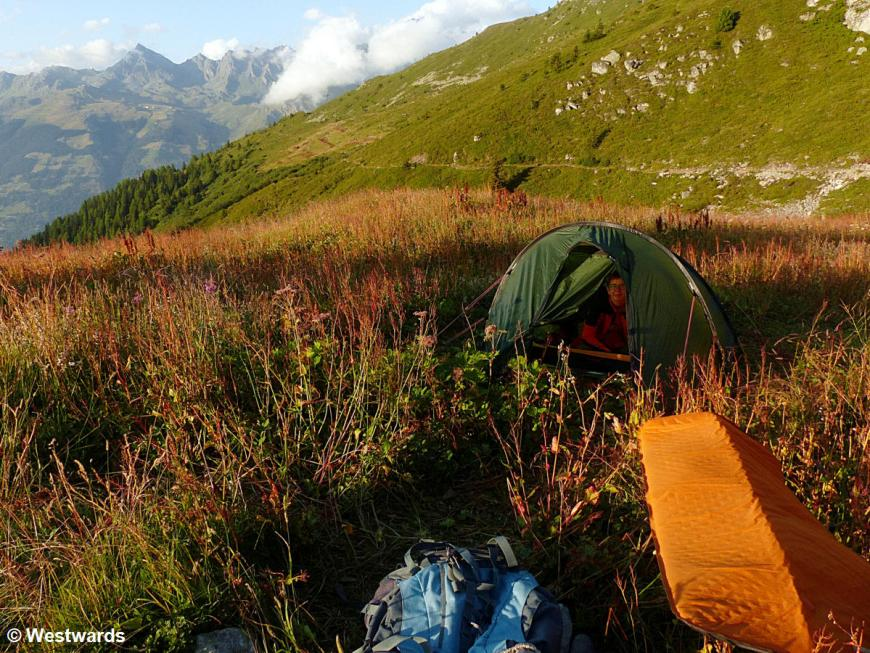 Tent and hiking gear in a mountain landscape