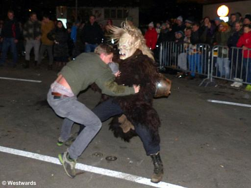 masked and unmasked man fighting