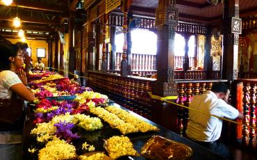 Beliefers offering flowers and praying at a Buddhist tempel