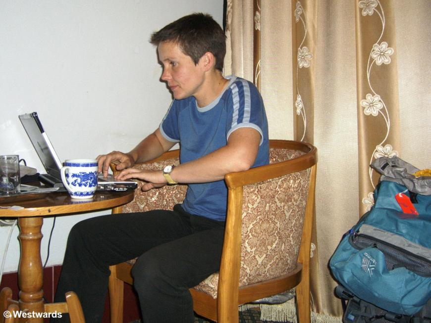 Isa working on the travel blog in a hotel room