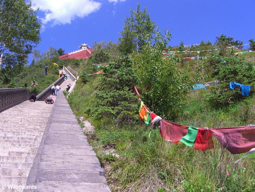 Outdoor stairs with prayer flags and praying pilgrims in Wutaishan