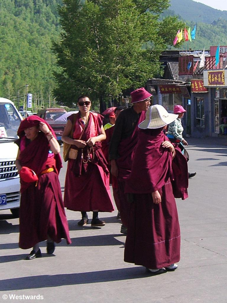Monks and nuns with red robes and sun glasses and sunhats in Wutaishan