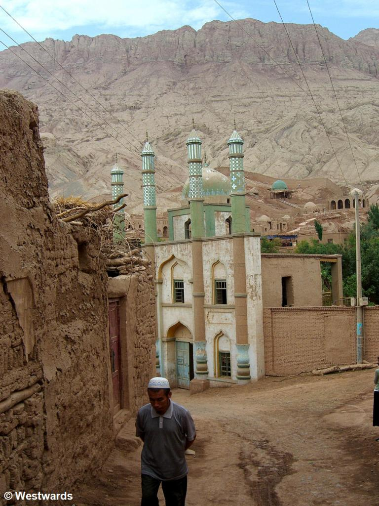Man with skullcap in front of a mosque near Turfan