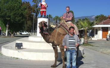 Santa Claus statue and tourist on a camel on a visit to Myra / Demre