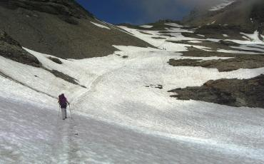 Hiker crossing a snow field on the way to Mont Buet
