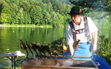 Man in traditional costume grilling fish at the shores of the lake