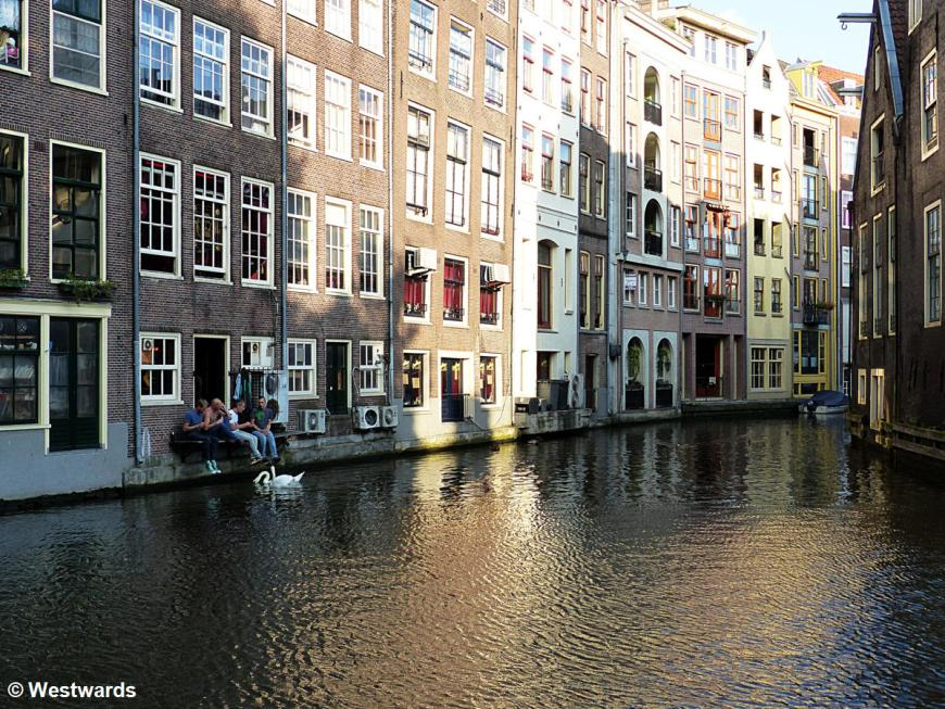 People sitting at the back of a house at an Amsterdam town canal