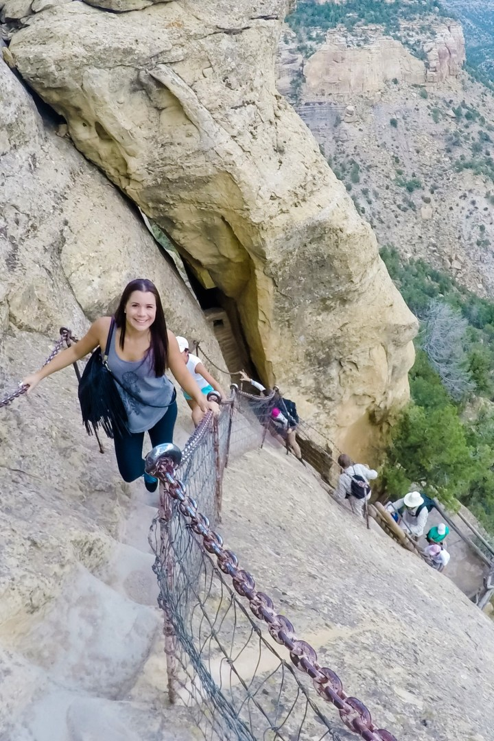 Woman climbing steep cliff on tour of Balcony House in Mesa Verde National Park, Colorado