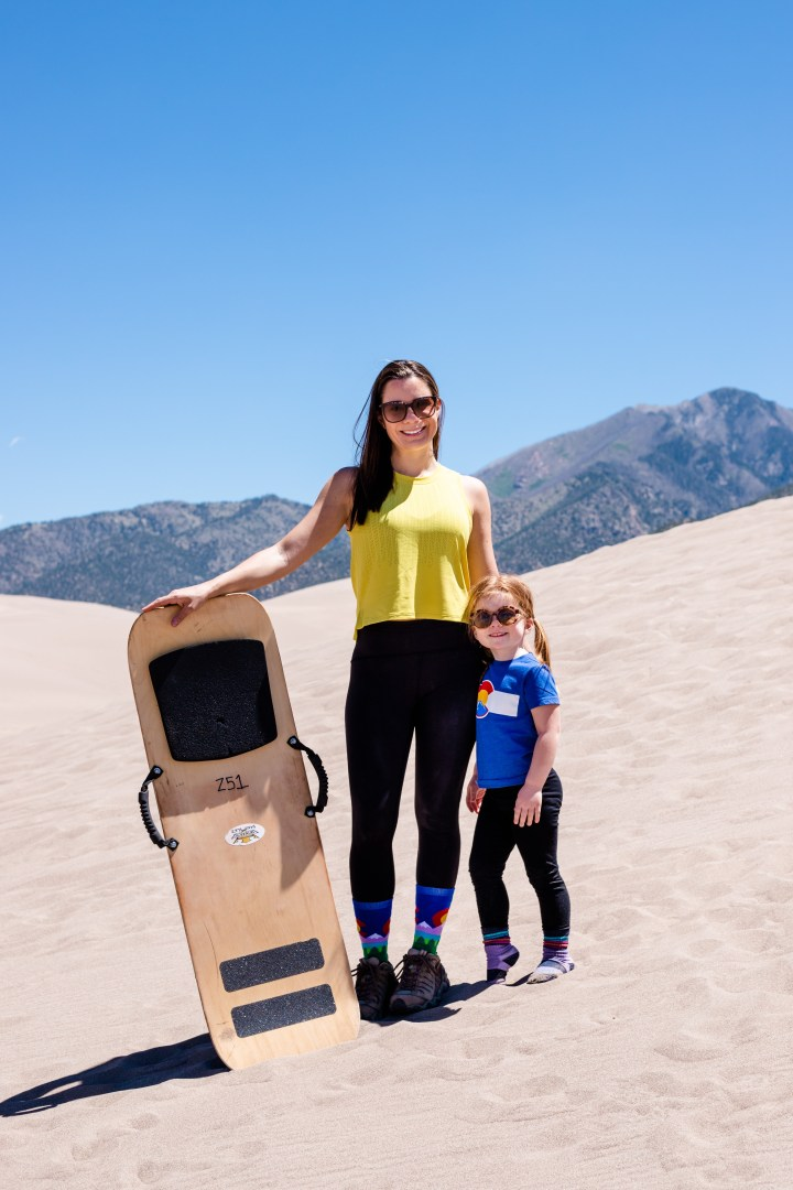 Woman and little girl with a sand board in Great Sand Dunes National Park and Preserve, Colorado