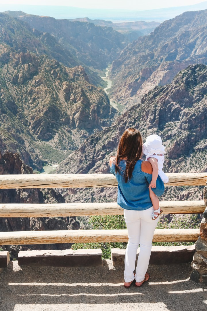 Mom and baby looking out at Black Canyon of the Gunnison National Park, rocky cliffs, craggy spires, Colorado