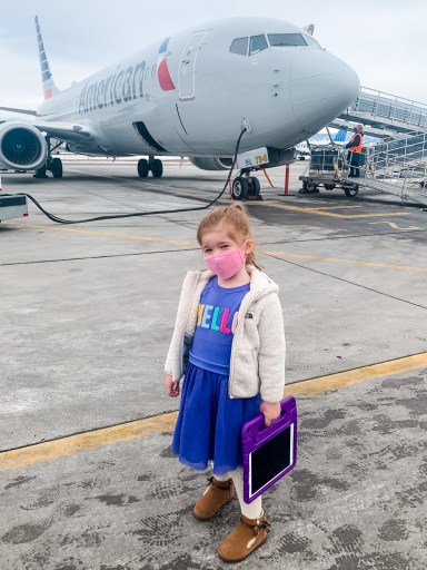 little girl with iPad and mask with American Airlines plane in Montrose, Colorado