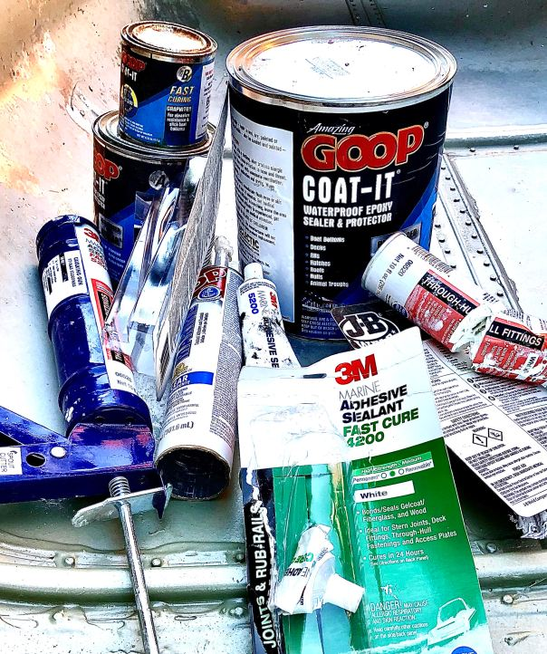 Image of 3M 5200vfast cure adhesive sealant, Coat-it epoxy sealer, j-B weld marine adhesive, GOOP marine adhesive sealant, and other marine sealants, in a pile, after being tested for efficacy.