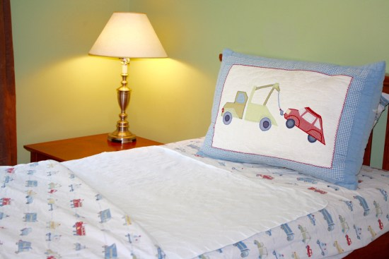 Child's bed with sheets and Wet-Stop waterproof bed pad in place.