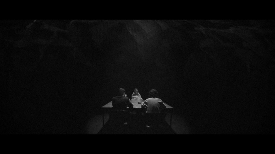A dark room with a table in the middle, two policemen are interrogation a woman