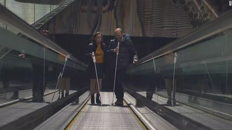 Two people at stairs with WeWALK