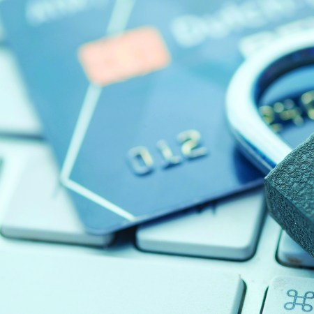 A lock and a credit card sit on a computer keyboard in this file photo.