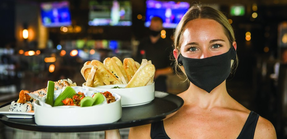 Waitress wearing mask and holding tray in restaurant