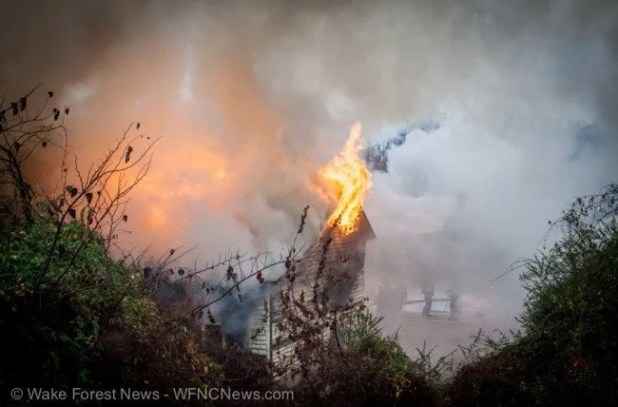 Fire leaps out of roof as firefighters prepare to pour on the water.