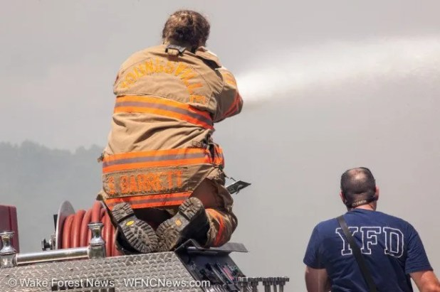 Youngsville firefighter Barrett controls the water cannon to hit the roof fire.