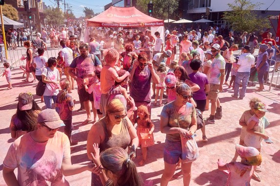 A crowd of people throwing Holi colour at one another
