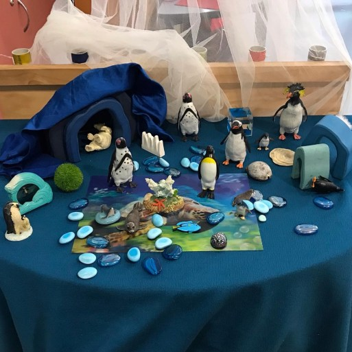 Table with arctic themed toys including penguins set up for play