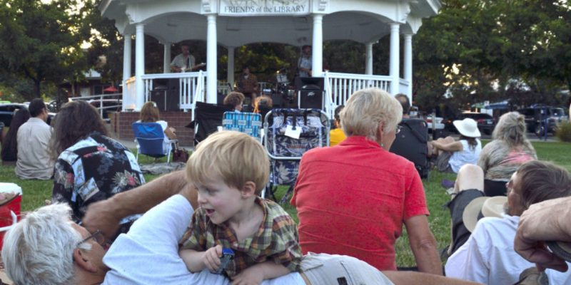 Crowd sitting on the lawn enjoying the Winters Friends of the Library Gazebo Concerts