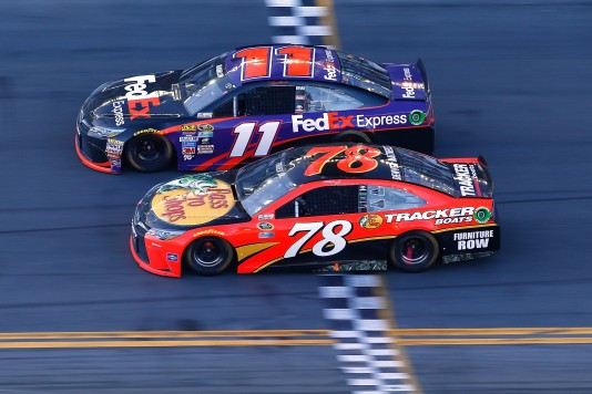DAYTONA BEACH, FL - FEBRUARY 21: Denny Hamlin, driver of the #11 FedEx Express Toyota, takes the checkered flag ahead of Martin Truex Jr., driver of the #78 Bass Pro Shops/Tracker Boats Toyota, to win the NASCAR Sprint Cup Series DAYTONA 500 at Daytona International Speedway on February 21, 2016 in Daytona Beach, Florida.  (Photo by Jonathan Ferrey/Getty Images)