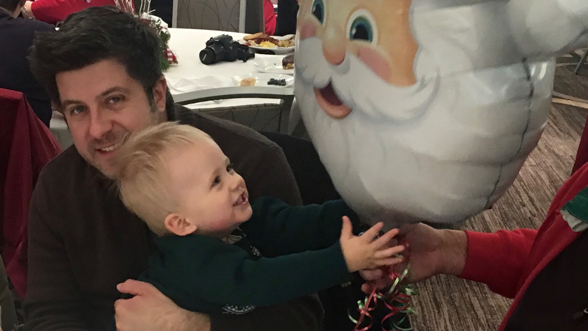 OTL host Mike Stephen III holds his son Mike Stephen IV... who enjoys Santa Claus balloons way more than he does the real Santa Claus.