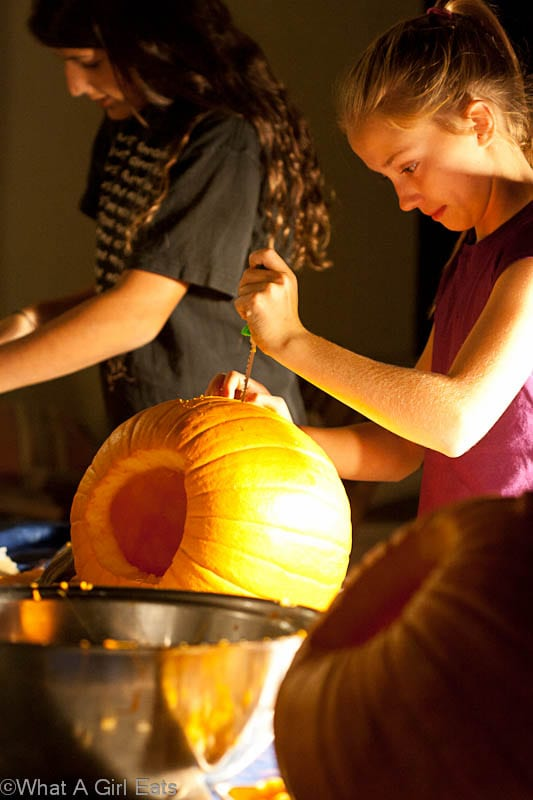 Young girls, having fun carving pumpkins (and later, eating roasted pumpkin seeds!)