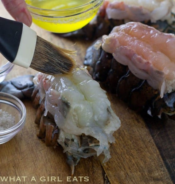 brushing lobster tails with butter before broiling