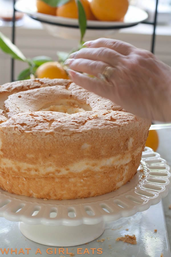 Orange cream angel food cake is a light, flavorful cake and perfect for a spring or summer dessert. With its refreshing citrus and vanilla flavors, this cake is reminiscent of a Creamsicle! | @whatagirleats