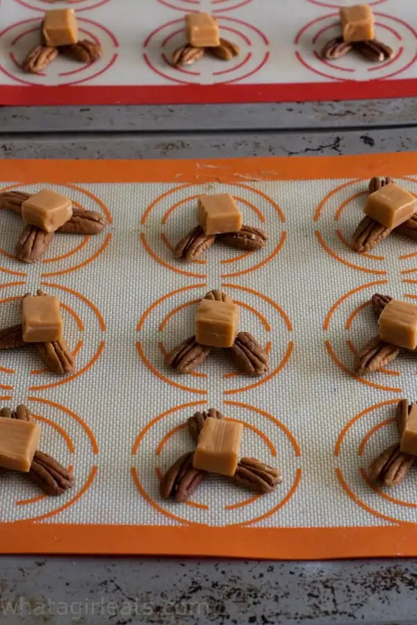 Arrange pecans in groups of 3. Top each cluster with a caramel candy.