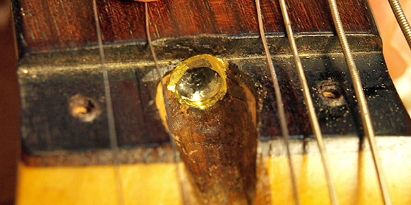 The truss rod socket end with ridges milled so a Torx bit can make the adjustment.