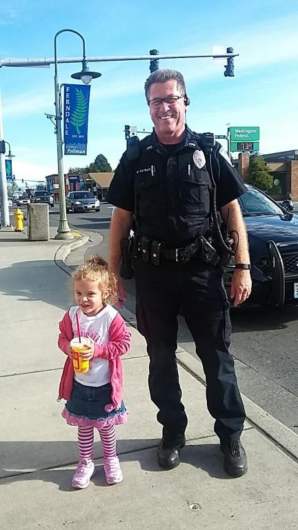 While investigating a crash on Main Street, Ferndale Police Officer Mike Catrain took time to pose with an admiring fan (September 25, 2016). Photo courtesy of Sarah Dalrymple.
