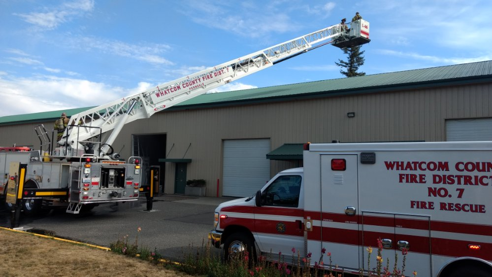 WCFD7 Ladder 46 personnel kept watch on the roof of a building in the Grandview Business Park while firefighters worked inside to tackle a fire (September 5, 2019). Photo: My Ferndale News