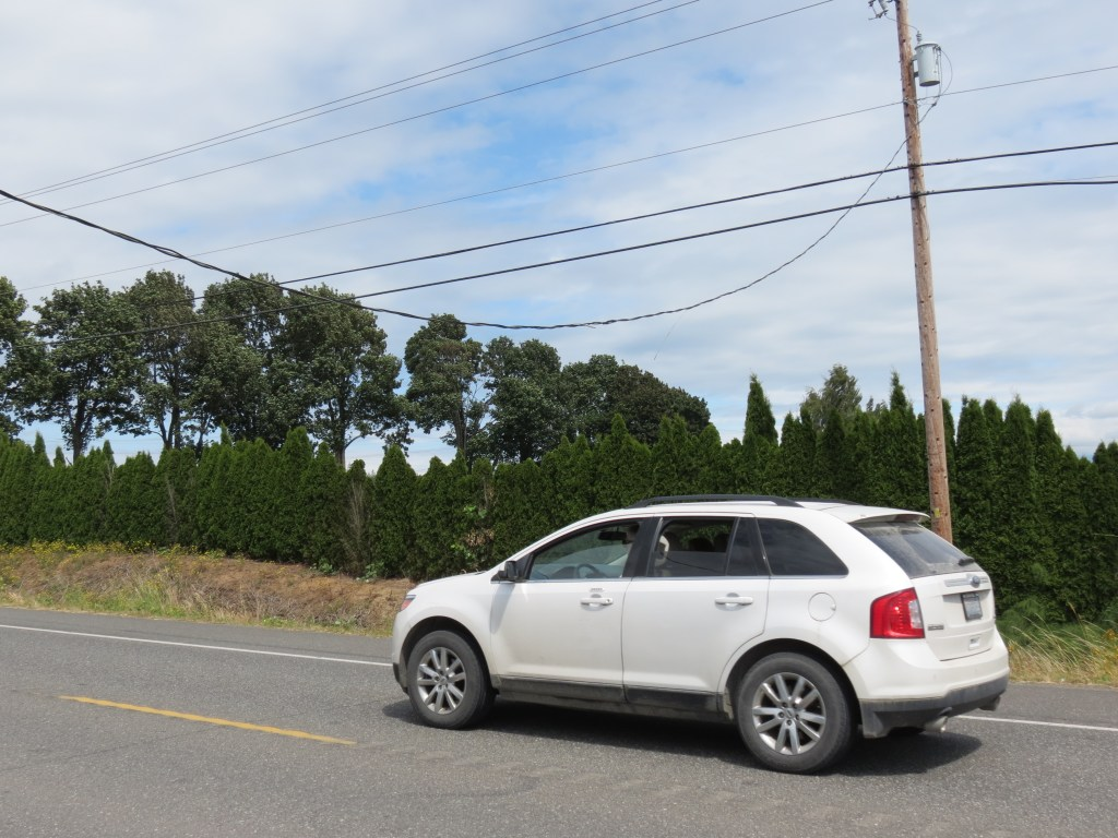A SUV passes under a low power line over Northwest Drive while law enforcement prevented tall vehicles from becoming entangled while awaiting repairs (July 23, 2020). Photo: My Ferndale News
