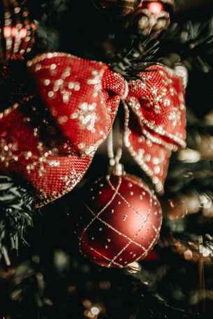 close up photography of a red and gold bow hanging on a christmas tree