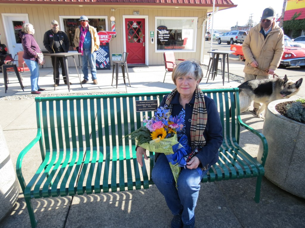 Nancy Knapp poses sitting on a bench dedicated to the memory of her husband, former Ferndale Chief of Police Michael Knapp (February 26, 2021). Photo: My Ferndale News