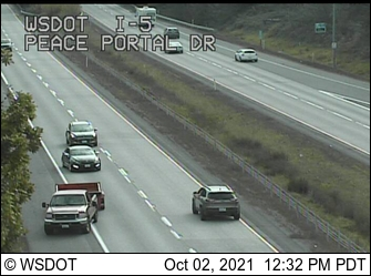 A vehicle traveling southbound in the northbound lanes of I-5 is seen as other drivers take evasive maneuvers to avoid crashing (October 2, 2021). WSDOT traffic camera