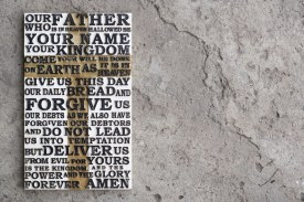 Wooden carved word of the Lord's Prayer on the grey concrete background.
