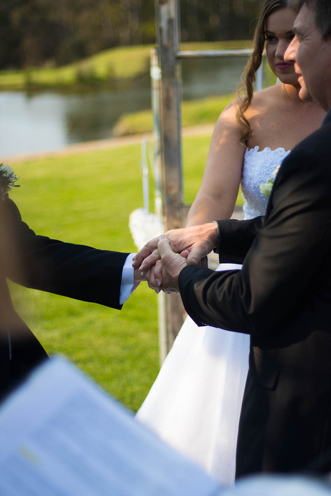 Father of the bride gives his daughters hand to groom at Clover Cottage Retreat, Manjimup