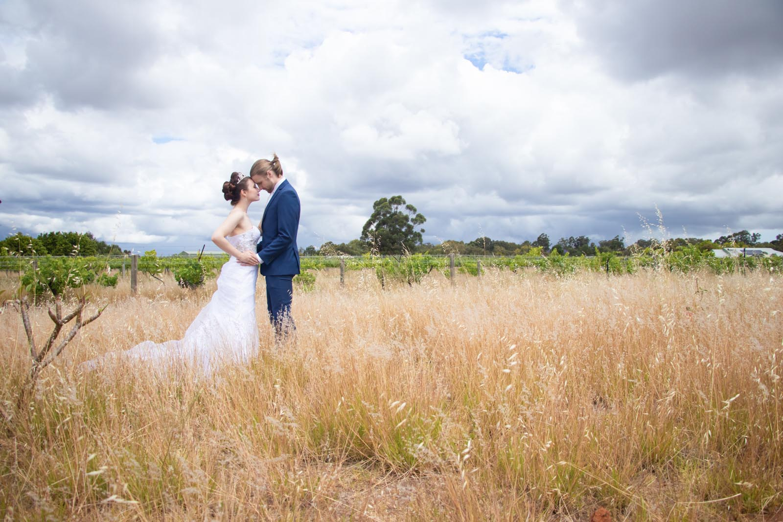 Bride and groom embracing in the field