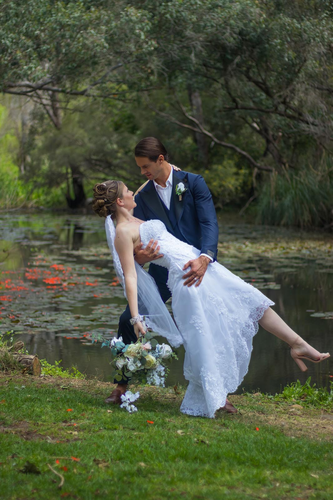 Groom holding his bride in a dip by the river