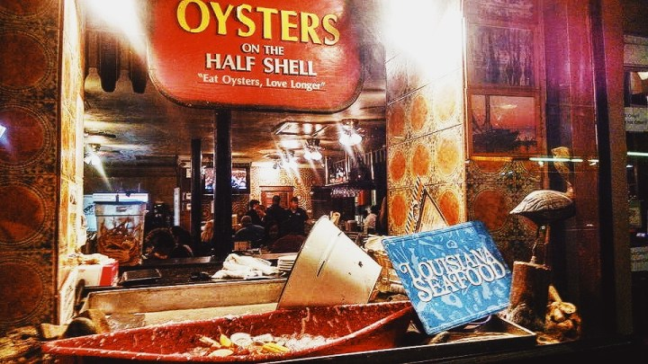 """A crawfish boil with pelican statue to the right and """"Oysters on the Half Shell"""" sign on top."""