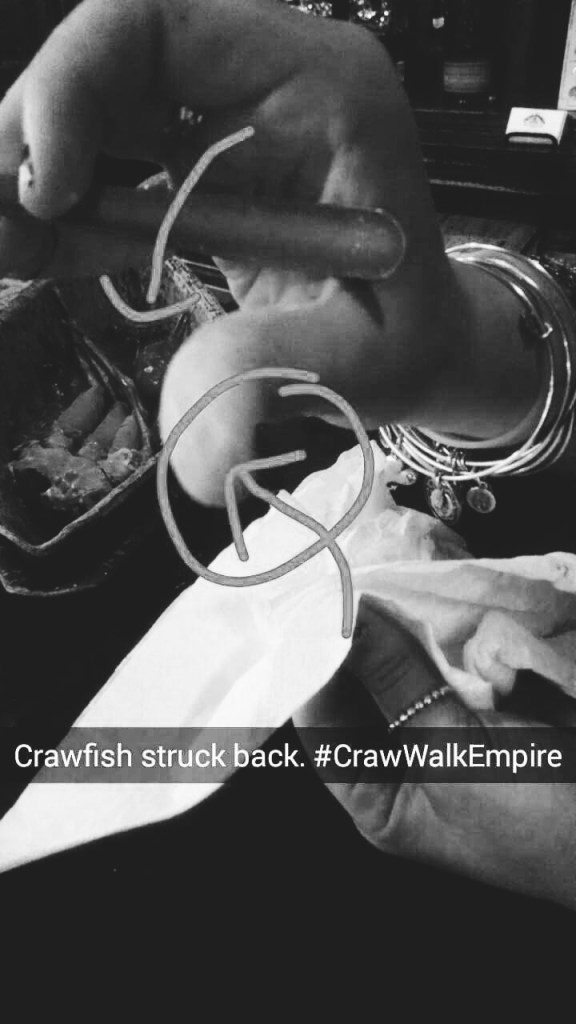 A woman being stabbed by a crawfish claw as she rummages through a bowl of them.